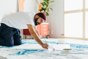 Male artist kneeling on the ground and painting
